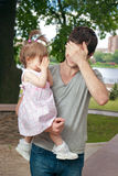 Young father holndig little daughter. In park stock photography