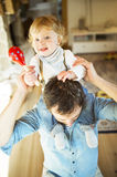 Young father at home giving his little son piggyback. Young father at home giving his little son piggyback, boy playing musical toy Royalty Free Stock Photography