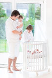 Young father with kids next tt white crib Stock Image