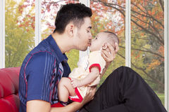 Young father kiss his kid on sofa. Happy father sitting on sofa while holding and kiss his baby, shot with autumn background on the window Royalty Free Stock Image