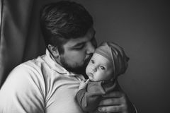 A young father kisses his newborn daughter. Father and newborn baby closeup stock image