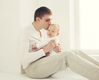 Young father kissing baby at home in white room Royalty Free Stock Image