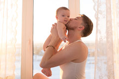 Young father kissing with baby son near the window Stock Image