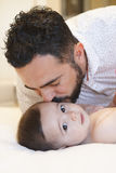 Young father kissing his cute baby boy with love. Father kissing his cute baby boy on his bedroom Royalty Free Stock Image