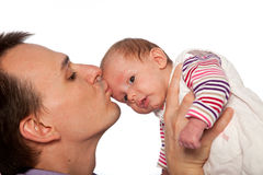 Young father kissing his cute little baby. Profile view of a loving young father kissing his cute little baby as he holds her aloft in the air while the infant Royalty Free Stock Image