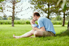 Young father kissing his funny newborn son outdoor. Portrait of young Caucasian father sitting on grass, holding funny newborn son and kissing him outdoor royalty free stock photos