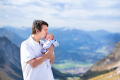 Young father kissing his newborn baby in mountains. Happy young father playing with his newborn baby in the beautiful snow covered mountains Stock Photos