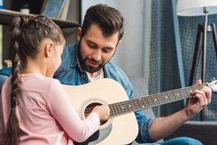 young father learning daughter to play guitar stock image