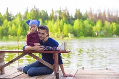 Young father and little adorable girl fishing on Royalty Free Stock Image