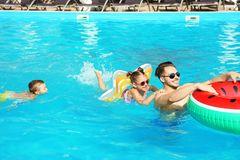 Young father with little children in swimming pool. On sunny day stock photography