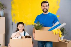 Young father and little daughter are planning to make house repair. Preparation house for sale. stock photo
