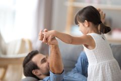 Father and daughter play together lying on couch holding hands. Young father and little daughter play together lying on couch in living room, close up focus on stock image