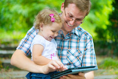 Young father and little daughter reading Stock Images