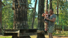 Young father with little daughter spend their leisure time in the rope park stock footage