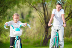 Young father and little girl biking at summer warm day. Young active family ride on bicycles Royalty Free Stock Photos