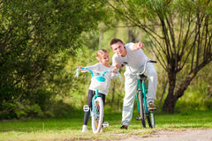 Young father and little girl biking at summer warm day. Young active family ride on bicycles Royalty Free Stock Photo