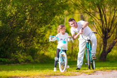 Young father and little girl biking at summer warm Stock Images