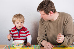 Young father and little son eating at home kitchen. Royalty Free Stock Image