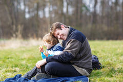 Young father and little son having picnic and fun near forest la Royalty Free Stock Photo