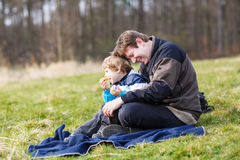 Young father and little son having picnic and fun near forest la. Smiling dad and little son having picnic and fun near forest lake, nature on cold spring or Royalty Free Stock Image