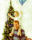 Young father with little son on his shoulders near New Year fir. Retro style photo at home Stock Photography