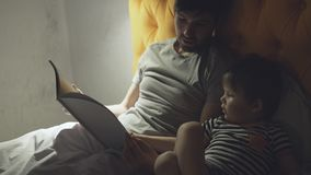 Young father with little son lying on bed at home and reading fairytale book before sleeping in evening. Time Stock Photo