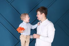 Young father and little son put out tongues for each other Royalty Free Stock Photography