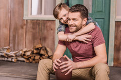 Young father with little son sitting on porch at backyard Royalty Free Stock Images