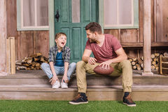 Young father with little son sitting on porch at backyard. Dad and son playing Stock Photo