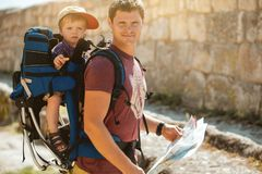 Young father with little son traveling in antic town. In crimea. Baby sits in backpack on the shoulders of his dad. Man using paper map royalty free stock photos