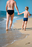Young father and little son walking at ocean beach Stock Photos