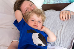 Young father and little toddler boy having fun in bed. Young father and little toddler boy having fun together in bed Royalty Free Stock Photos