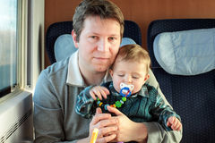 Young father and toddler boy sitting in train Royalty Free Stock Images