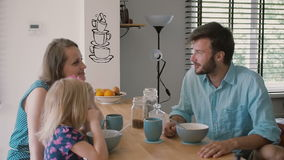 Young father is looking at his wife and daughter at the kitchen table during breakfast. Slow motion, Steadicam shot stock video