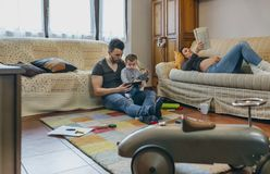 Father looking tablet with little son while the pregnant mother reads a magazine Stock Photography
