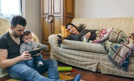 Father looking tablet with little son while the pregnant mother watches television Stock Images