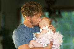 Young Father Lovingly Hugging and Kissing Baby Daughter. A happy young father is lovingly hugginghis baby daughter and kissing her forehead Royalty Free Stock Photo