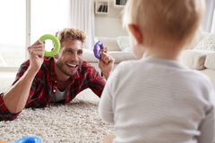 Young father lying on floor playing with toddler son at home royalty free stock photo
