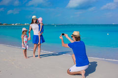 Young father making photo on phone of his family at the beach Royalty Free Stock Photos