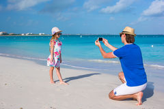 Young father making photo on phone of little girl Royalty Free Stock Photo
