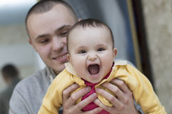 Young father man holding and hugging in his arms child baby kid girl smilling laughing royalty free stock photography