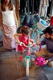 Young father and mother choice new bicycle for little girl in bike shop top view royalty free stock image