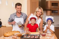 Young father and mother making cake together. Royalty Free Stock Photos