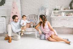 Young father and mother playing with son and cats. In white loft Royalty Free Stock Photo