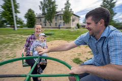 Young father and mother with son 1.3 years riding on  carousel. Royalty Free Stock Photography