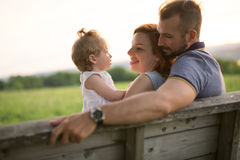 Young father and mother with their cute daughter sit on a bench at the sunset Royalty Free Stock Photography