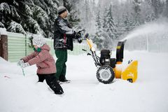 Young father operates snow blower Royalty Free Stock Images