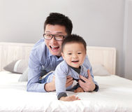 Young father play with his son boy. On the bed at home, asian lifestyle Royalty Free Stock Photography