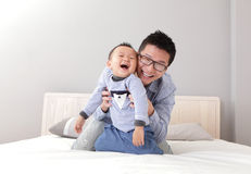Young father play with his son boy. On the bed at home, asian lifestyle Royalty Free Stock Photo