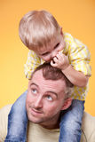 Young father play with son on his shoulders. Young father playing with son on his shoulders Stock Image
